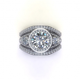 14kt white gold wedding set that has a round brilliant cut center diamond with a halo surrounding it, there are diamonds going down either side and tapering at the bottom of the ring. There are two wedding bands that contour to fit up against the engagement ring, they have shared prong diamonds going across the top of each one.